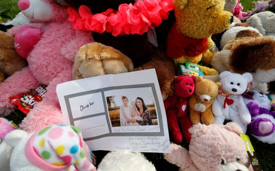 A photograph sits amid the tributes as they grow outside the home where a pregnant woman, Shanann Watts, and her two daughters, Bella and Celeste, lived Thursday, Aug. 16, 2018, in Frederick, Colo. The woman's husband, Christopher Watts, has been arrested on suspicion of killing his family.