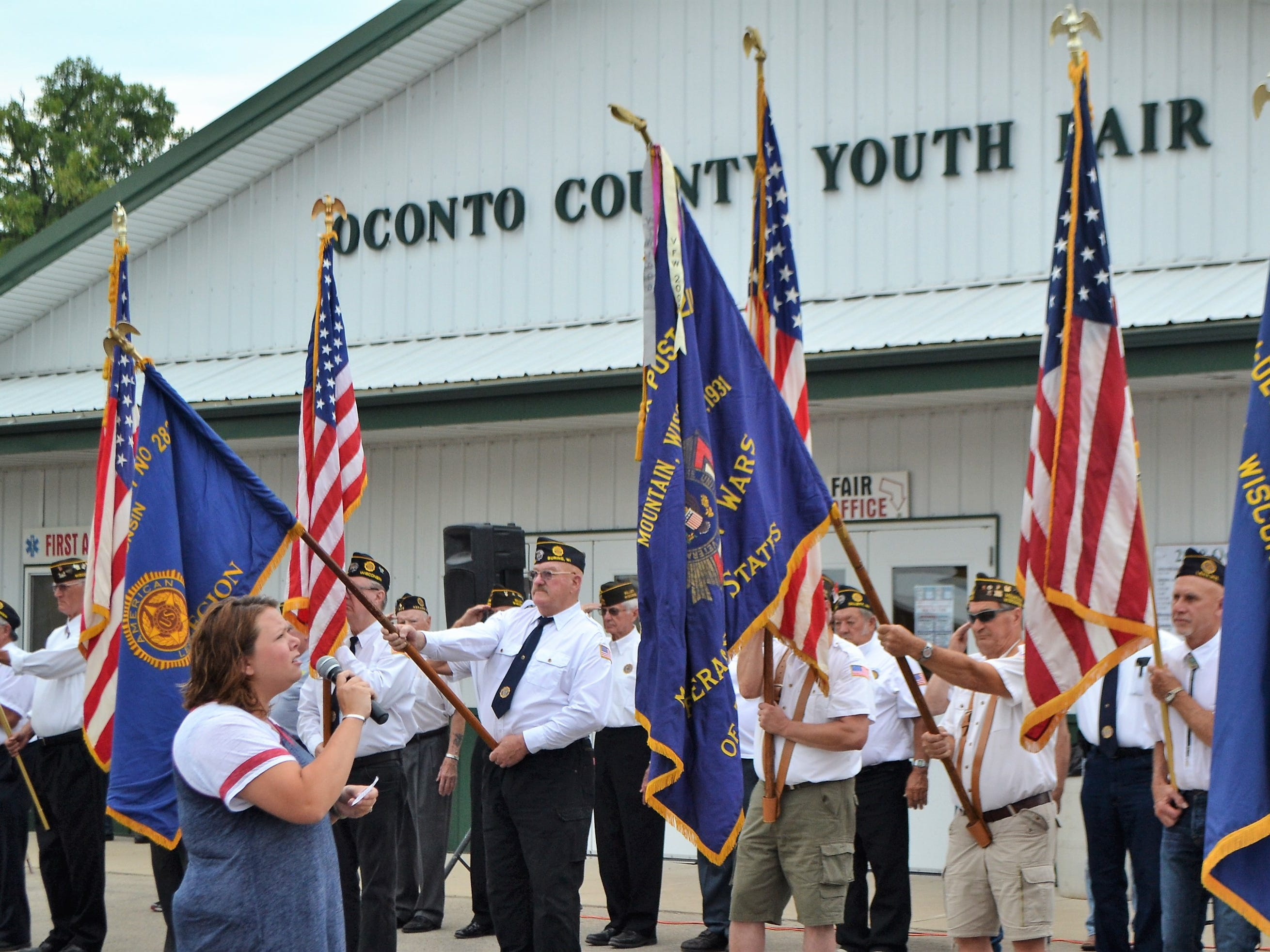 Kari Moody sang the National Anthem as a color guard of veterans from Oconto County hold flags at the opening ceremony of the Oconto County Fair on Thursday, Aug. 16.