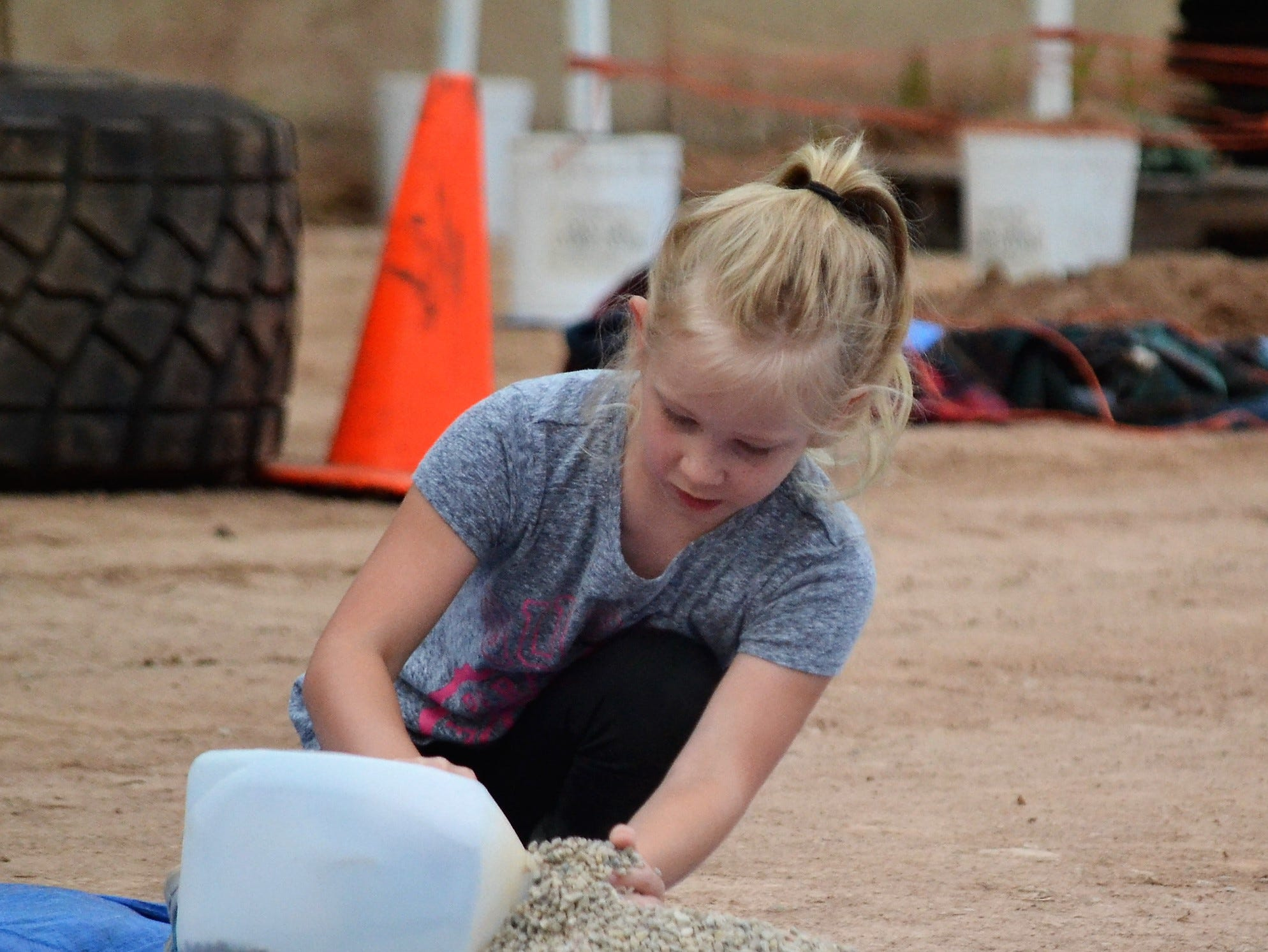 Emily Peterson of Oconto Falls fills a milk jug with pea gravel in a one of the competitions at the Ag Olympics on Thursday, Aug. 16 at the Oconto County Fair.