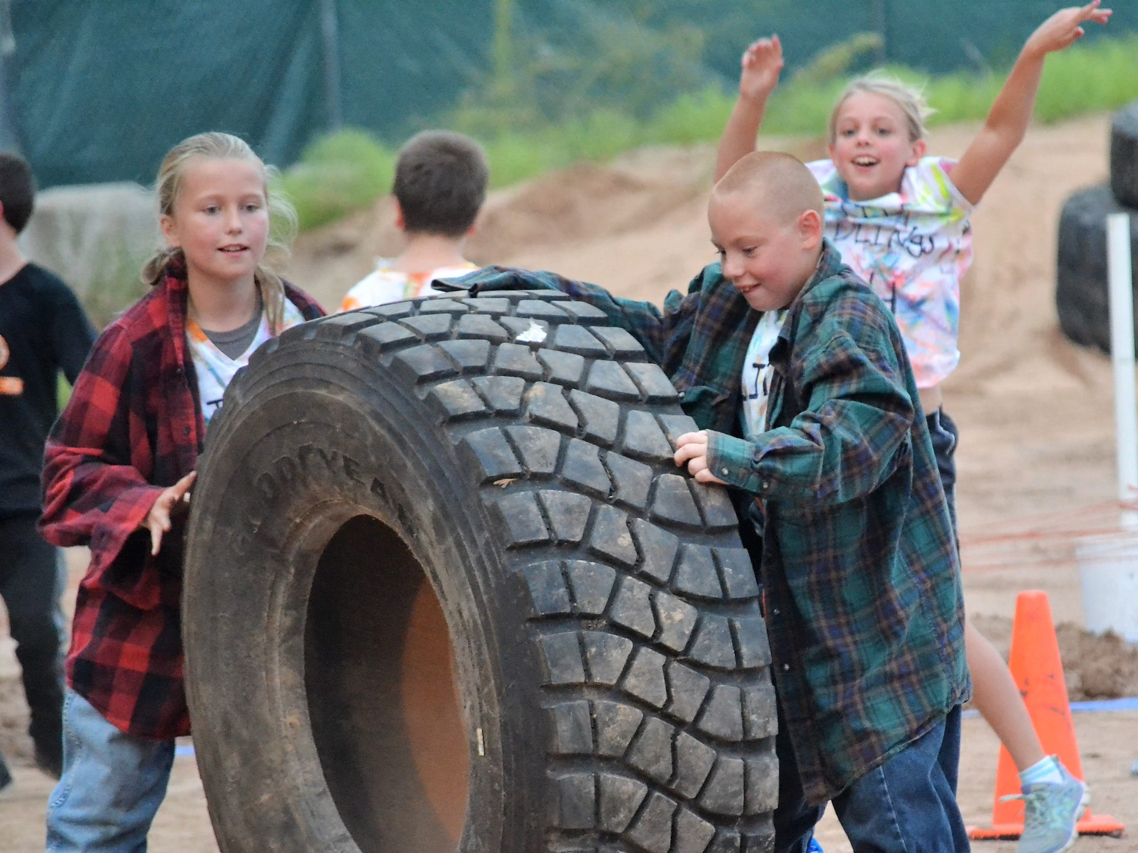 "Audrey Pate of Cecil and Jack Schindler of Underhill work together to maneuver a tractor tire around a course in an Ag Olympics event at the Oconto County Fair on Thursday, Aug. 16. Before rolling the tire, they first had to dress up in ""farmer clothes"" -- flannel shirts, jeans and booties."