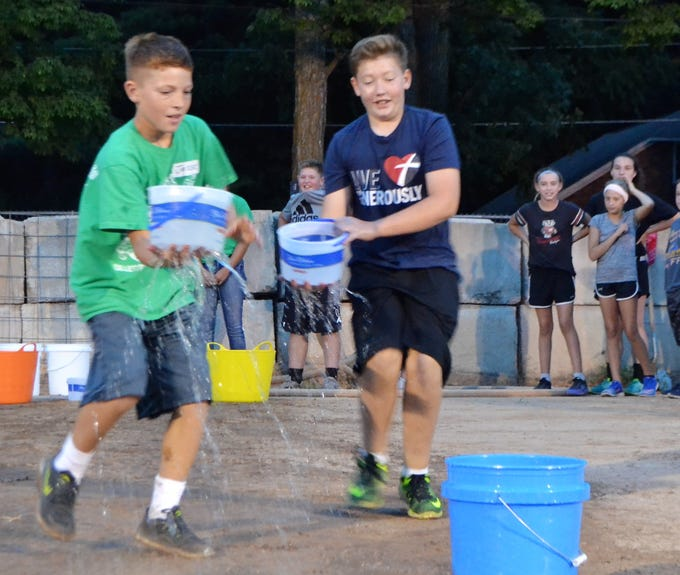 Jesse DeBauch and Brandon Bjelland, both 12 and from Gillett, race to fill a five-gallon pail in one of the events from the Ag Olympics at the Oconto County Fair on Thursday, Aug. 16. The task was made more difficult because holes had been punched in the bottom of the ice cream buckets used to transfer the water.