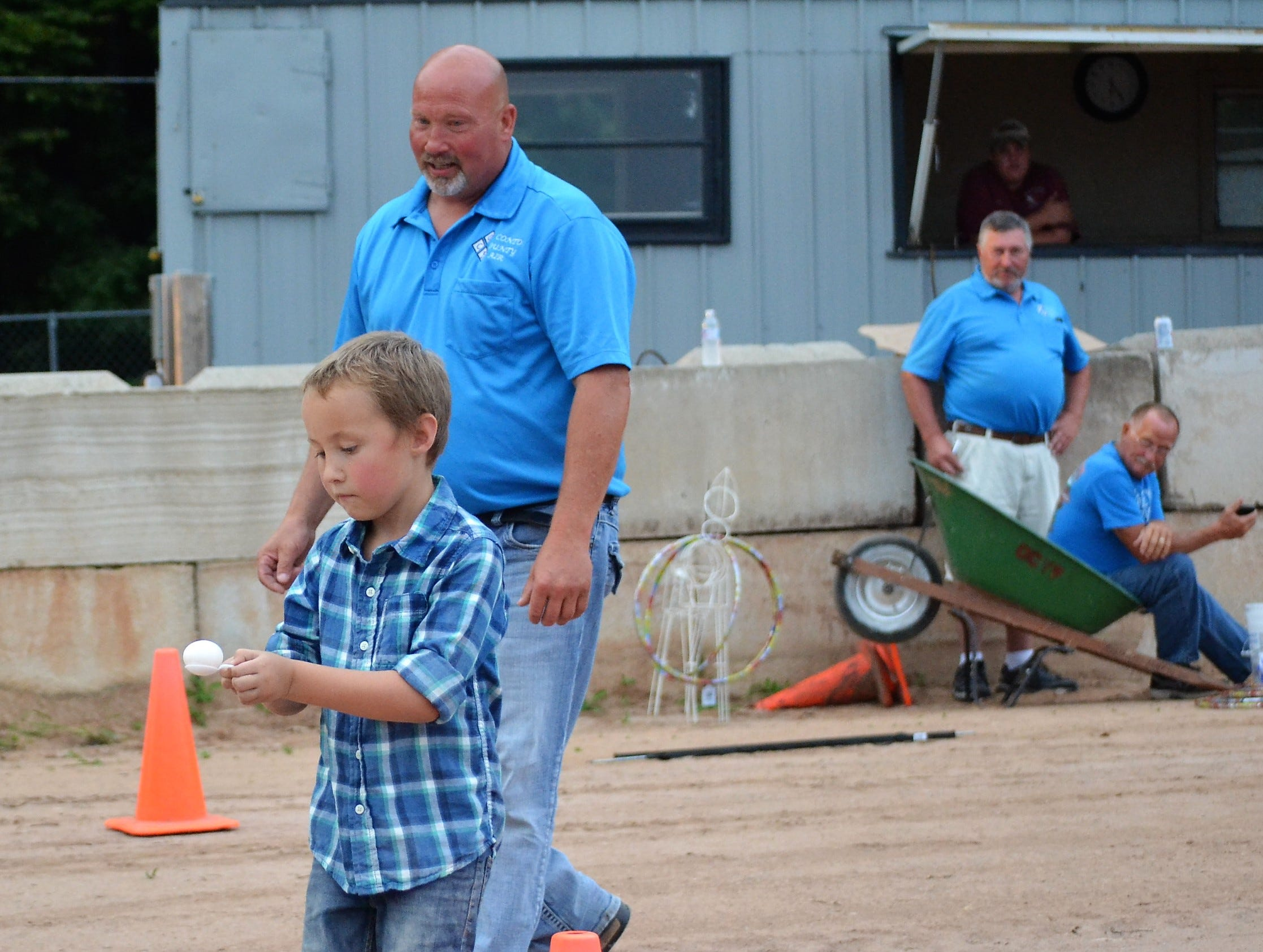 Walker School of Suring carefully carries an egg on a spoon at his negotiates cones on the track at the Oconto County  Fair on Aug. 16 in an Ag Olympics events. Behind him is Fair Board president Chris Engebretsen, left, and other fair board members.