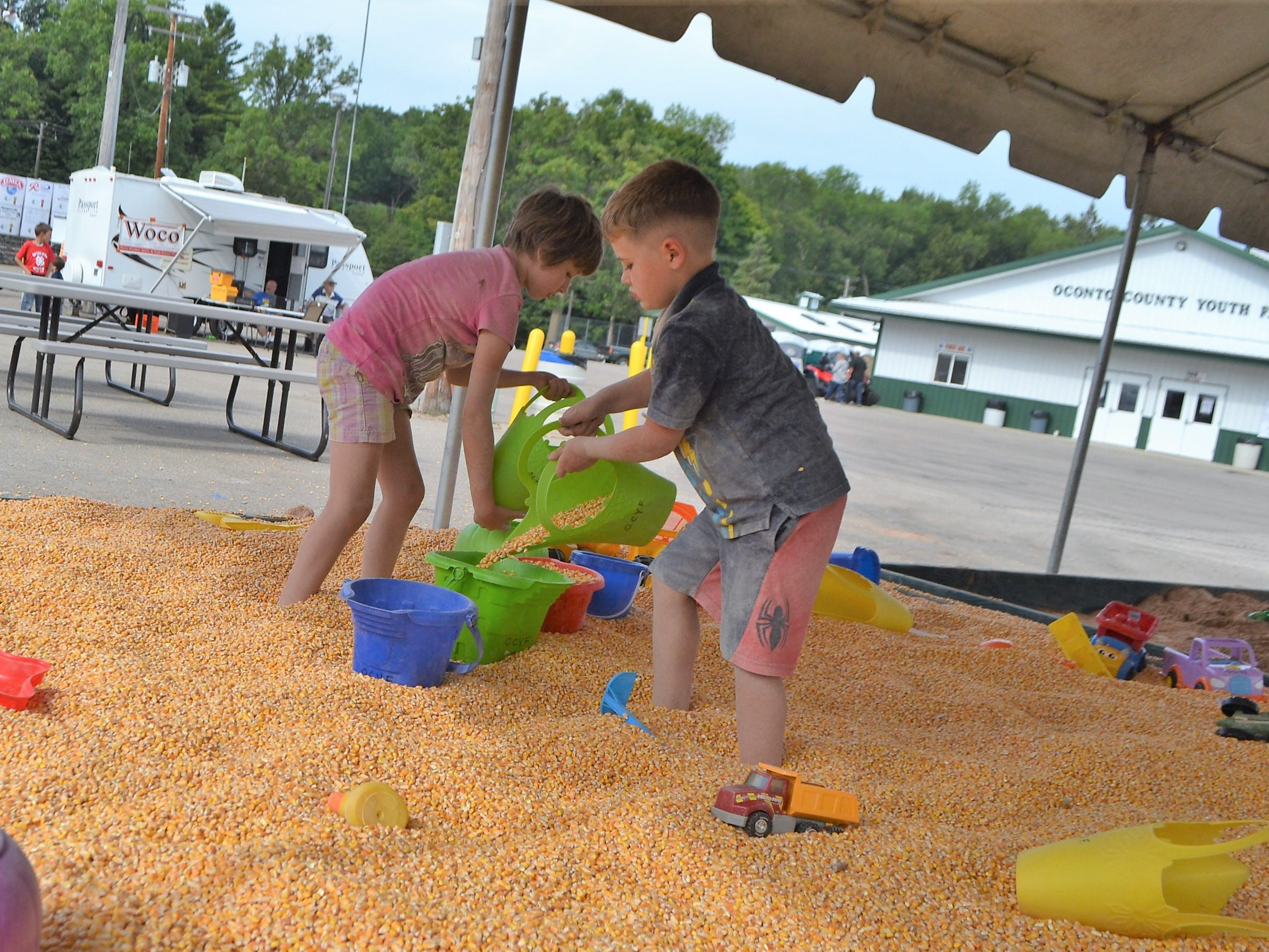 Peyton Williams, 7, and her brother Brandon, 5, were among the many children who enjoyed playing in the corn box at the Oconto County Fair on Thursday, Aug. 16. The corn box is new this year,  while the adjacent sandbox, which also was getting plenty of use, was first set up last year.