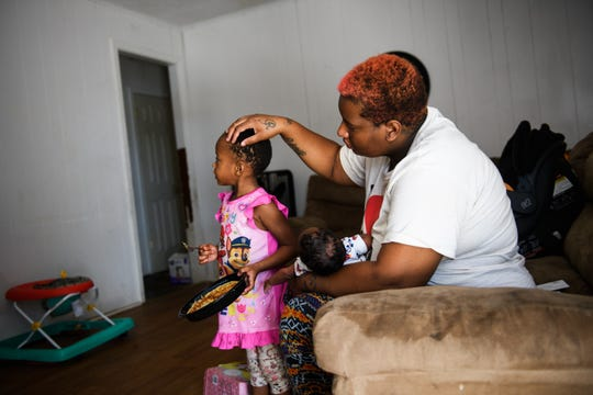 Teonna Williams strokes her daughter Na'Zorah's hair in her apartment on Saturday, Aug. 11, 2018.