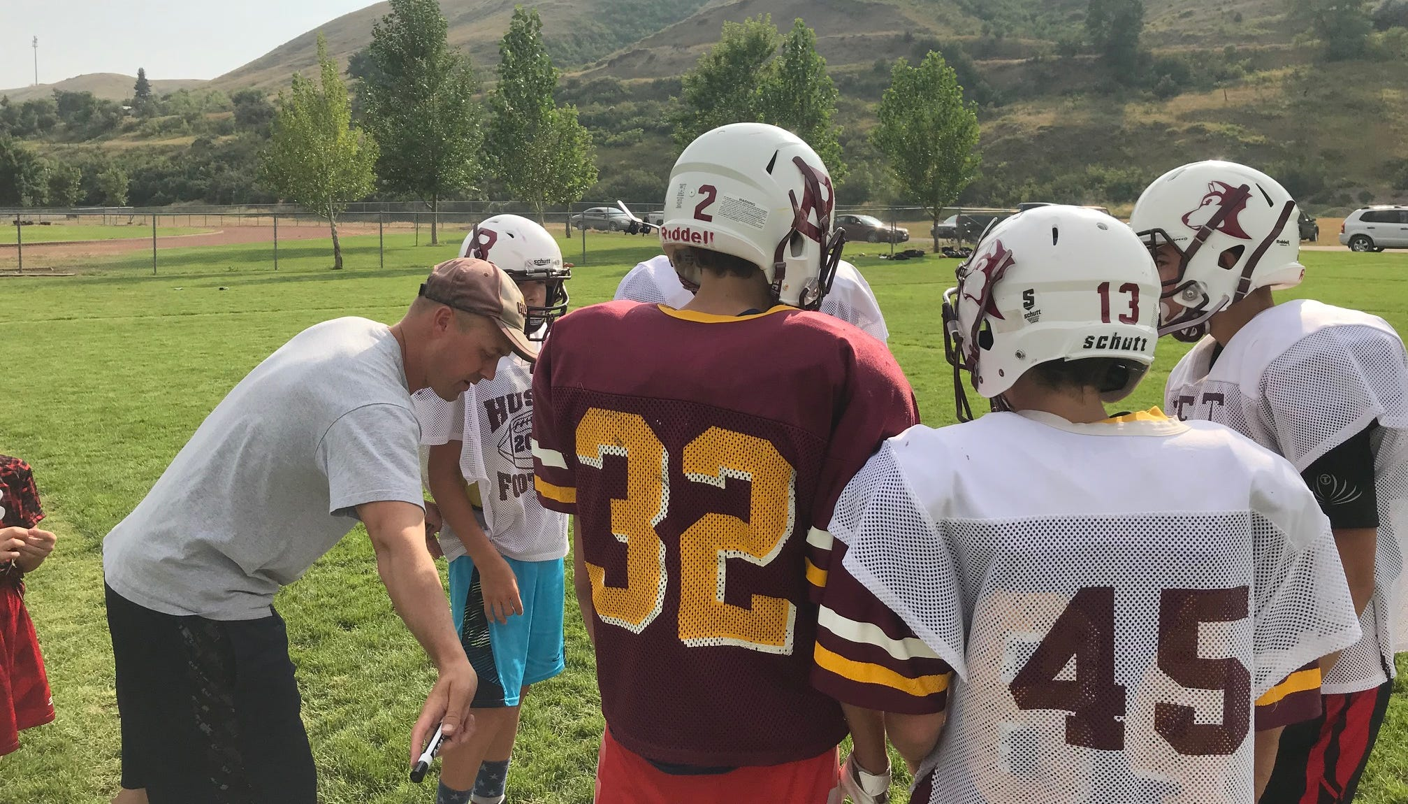 Jeff Graham, in t-shirt at left, instructs his Belt Huskies offense on a play during a recent practice.