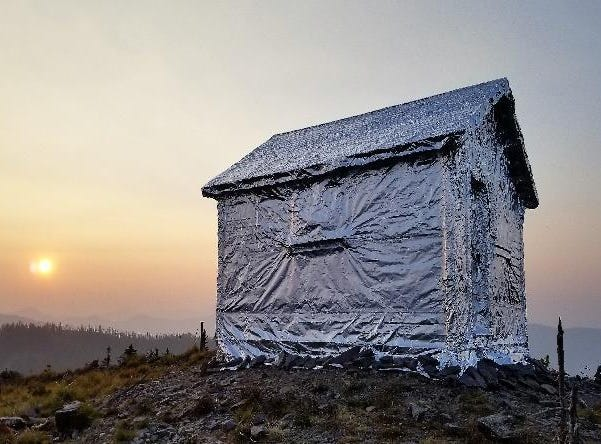A forest service patrol cabin in the Coal Ridge Fire area, burning 10 miles west of Polebridge, is wrapped with fire resistant material.