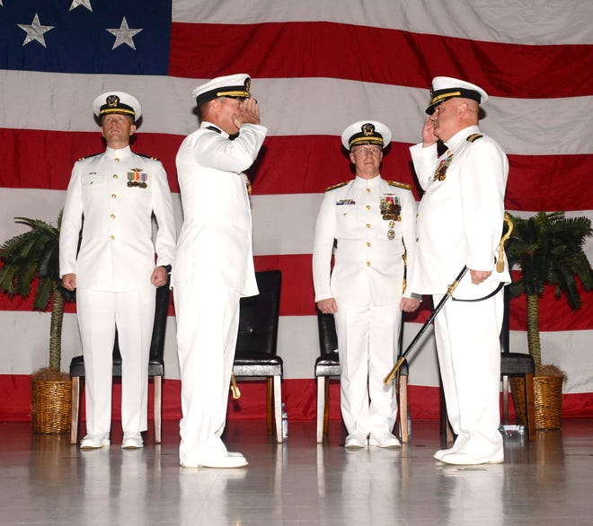 Capt. Timothy Poe, right, relieves Capt. David Schappert, left, as commander, Submarine Squadron 15 during a change of command ceremony at the Naval Base Guam theater Aug. 17. The squadron is located at Polaris Point on Naval Base Guam and consists of four Los Angeles-class attack submarines.