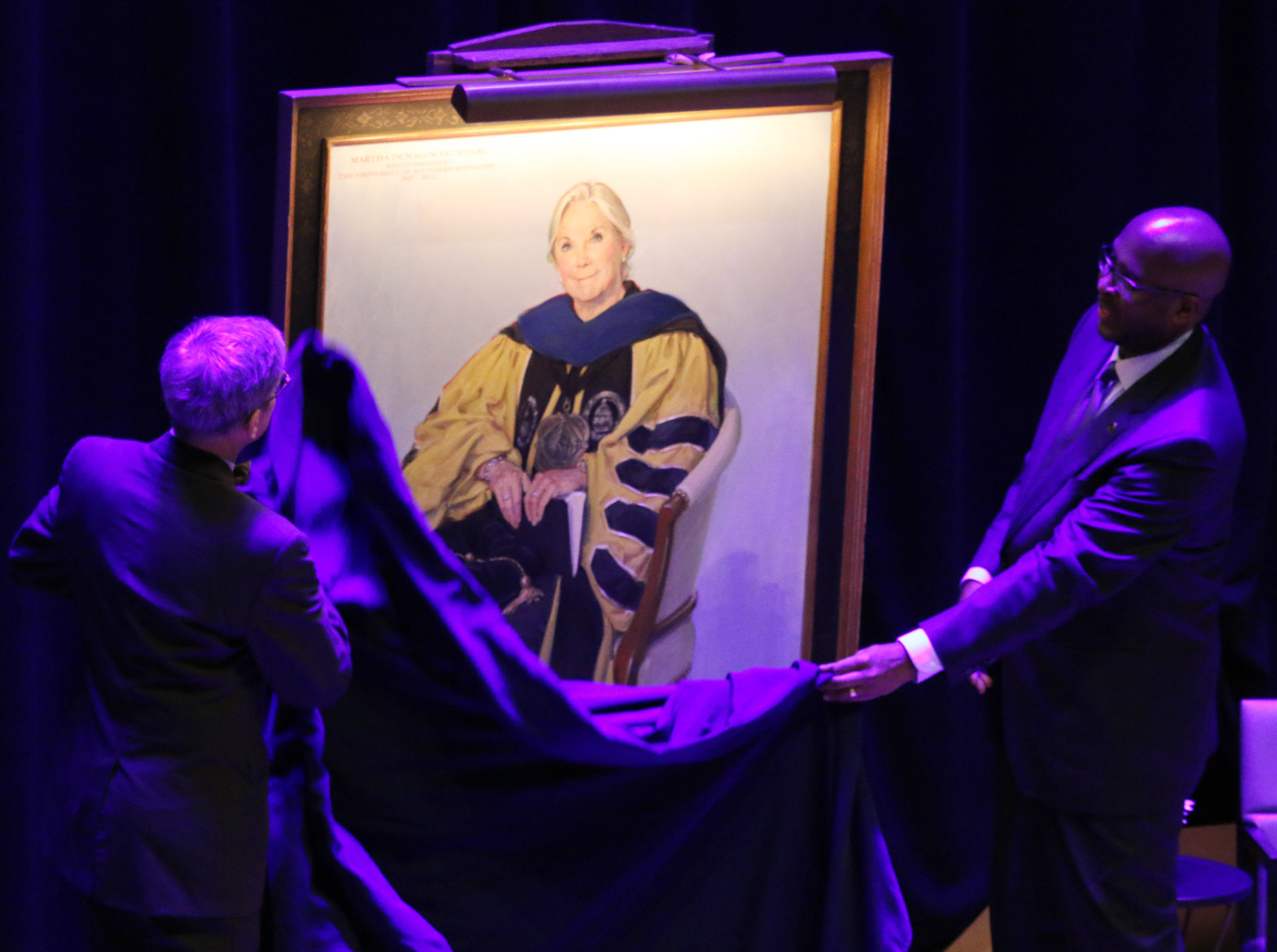 Artist Jason Bouldin, left, and President Rodney Bennett, right, unveil the portrait of Martha Saunders at Southern Miss Friday.