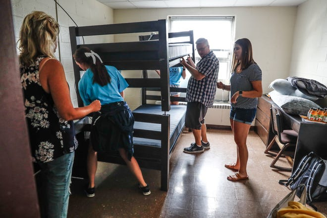 Left to right, Tammy Coil, Hannah Denney, Leslie Toon, Dave Coil, and Anna Coil rearrange bunk beds in a dorm room during move-in day at Marian University in Indianapolis on Friday, Aug. 17, 2018. Student-athletes in organized teams helped students and parents move into dorm rooms.