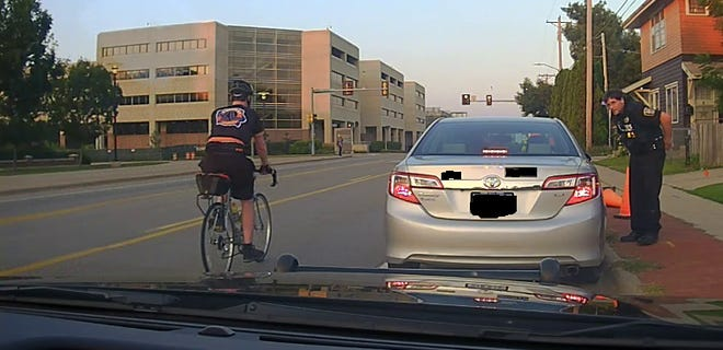 Dash cam video shows University of Heights police pulling over a car on Melrose Avenue and a cyclist at the car's side.