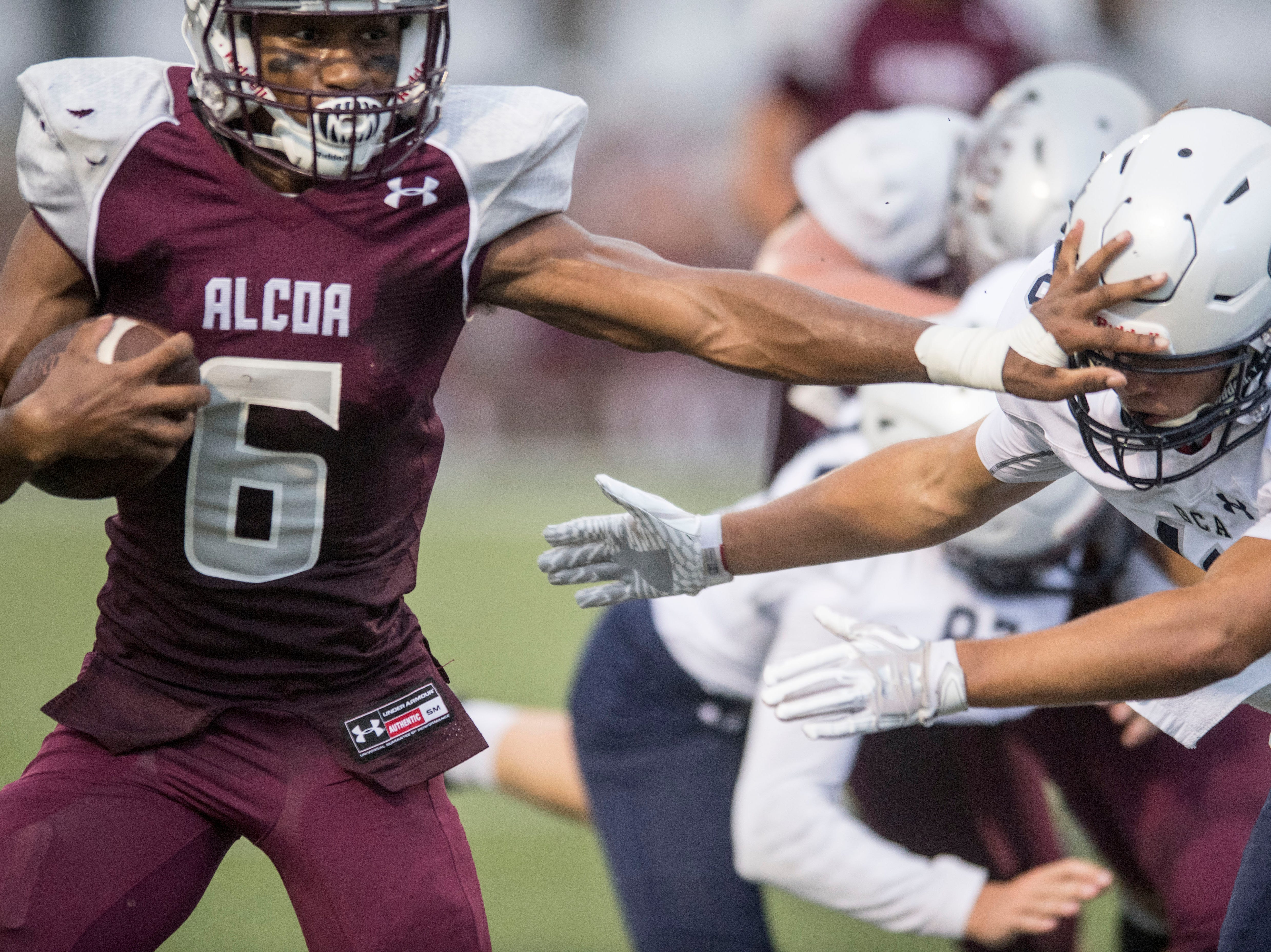 Alcoa's Kareem Rodriguez (6) tries to hold back Grace Christian Academy's Cooper Riggs (18) during the footbal game at Alcoa football on Thursday, August 16, 2018.