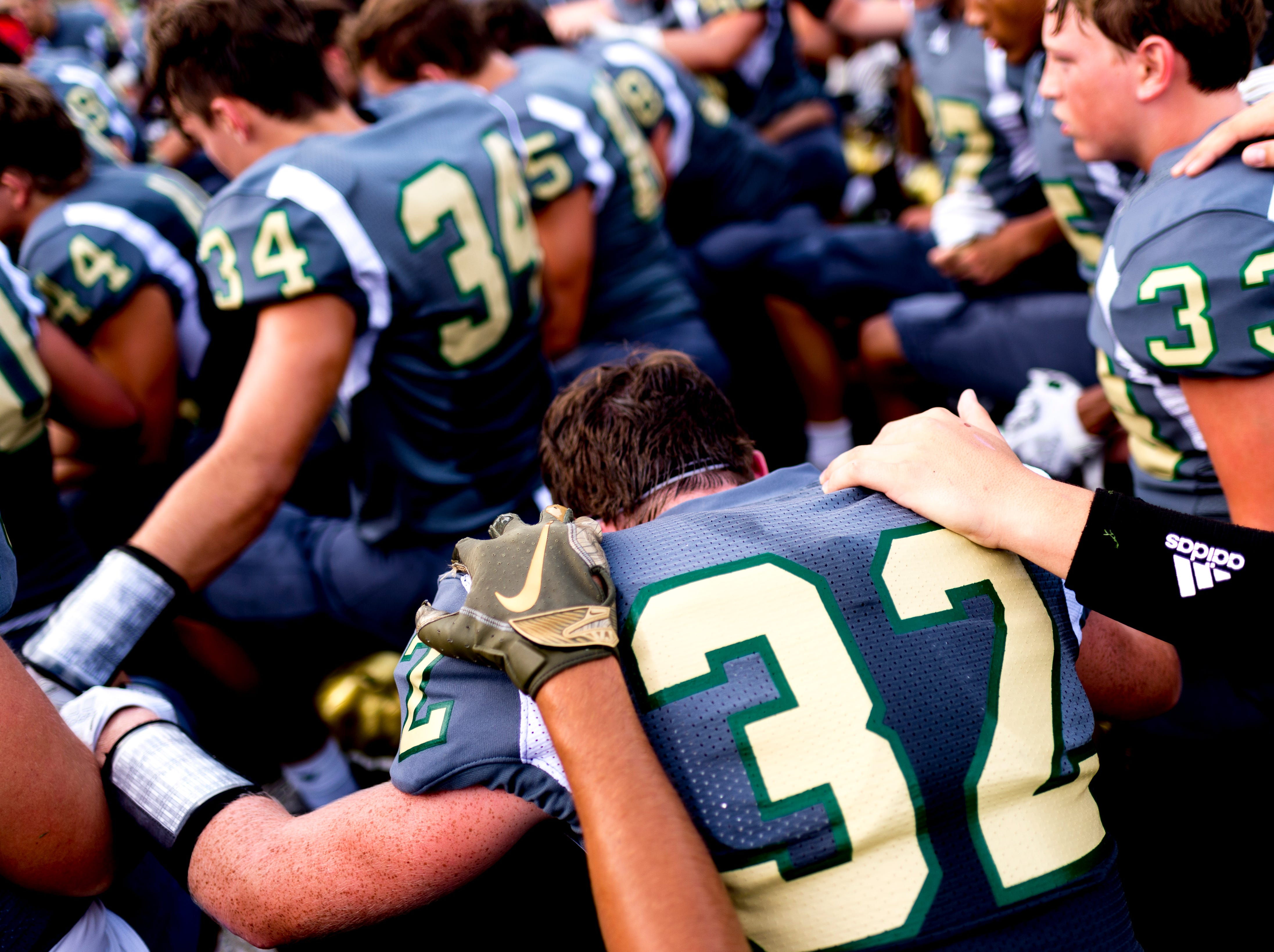Catholic's Spencer Margolis (32) says a prayer with fellow teammates during a football game between Maryville and Catholic at Catholic High School in Knoxville, Tennessee on Friday, August 17, 2018.