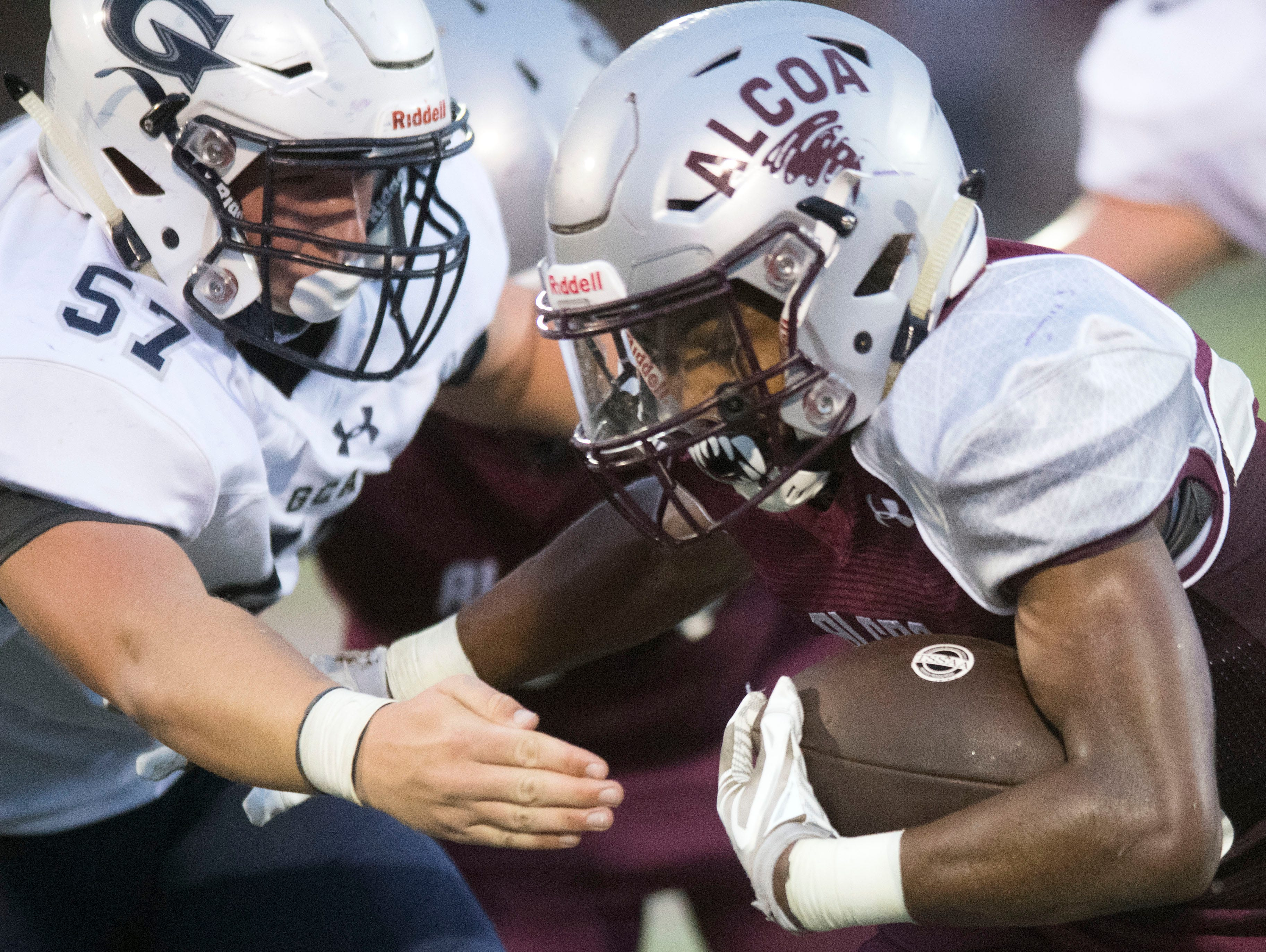Alcoa's J.R. Jones (28) is tackled by Grace Christian Academy's Lucas Ellis (57) during the football game at Alcoa on Thursday, August 16, 2018.
