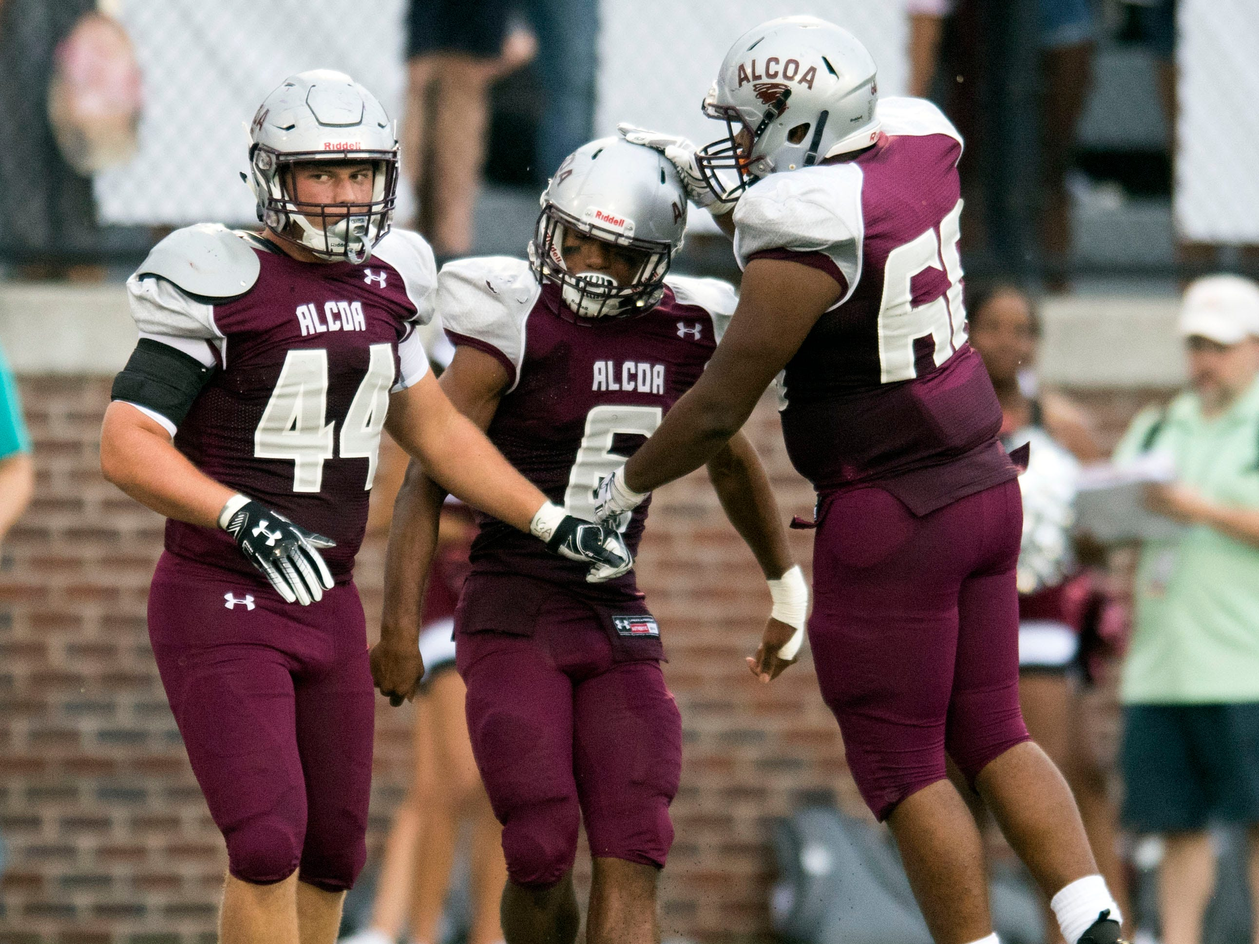 Alcoa's Landon Ray (44), left, and Jakobe Robinson (60), right, congratulate teammate Kareem Rodriguez (6) for scoring a touchdown in the football game against Grace Christian Academy on Thursday, August 16, 2018.