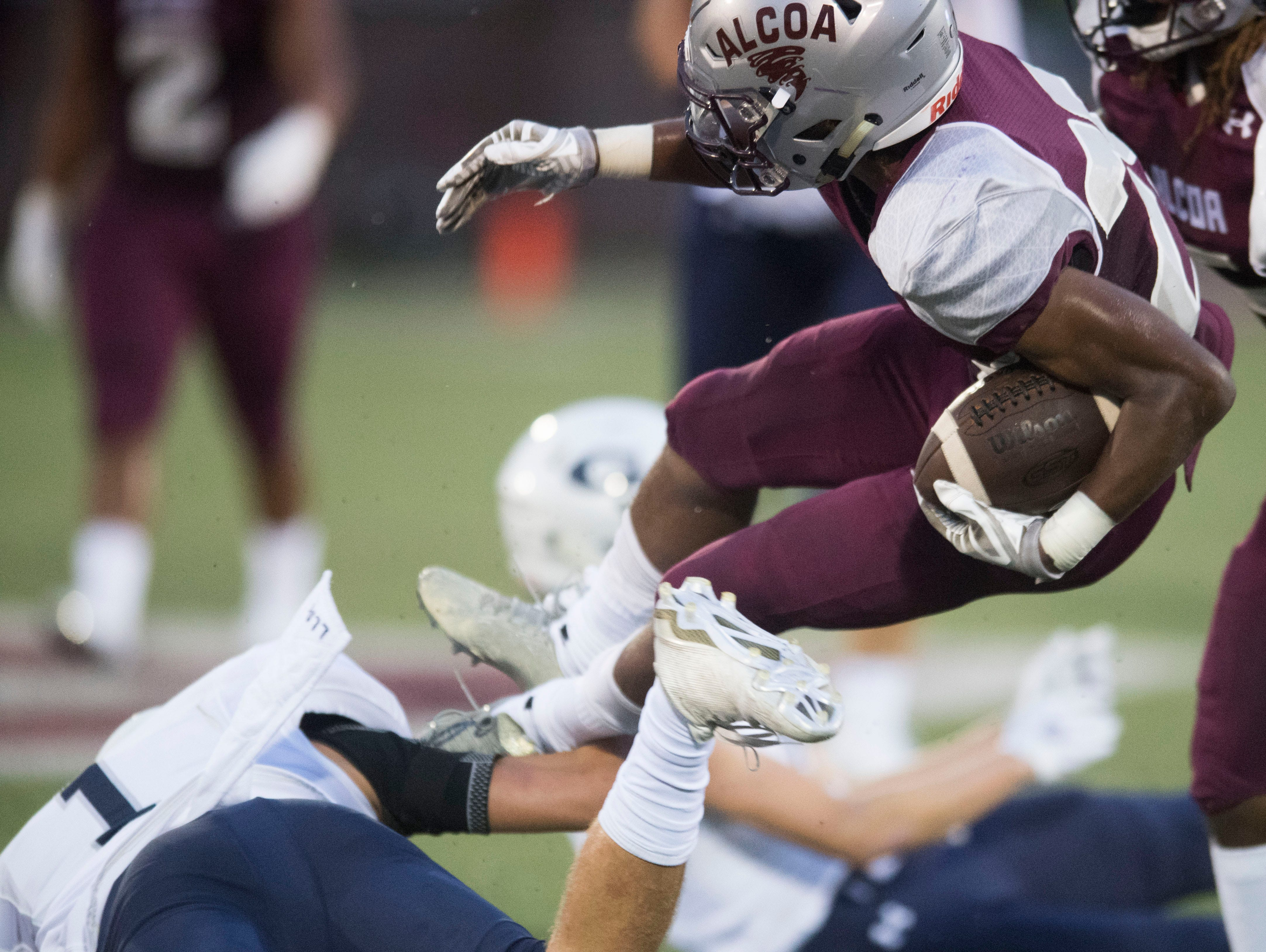 Alcoa's J.R. Jones (28) is tripped up by Grace Christian Academy's Michael Feiden (1) during the football game at Alcoa on Thursday, August 16, 2018.