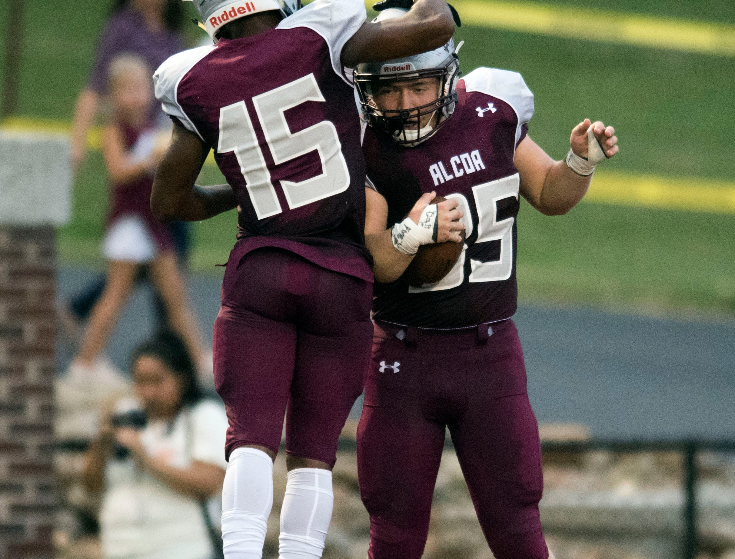 Alcoa's Ahmaudd Sankey (15) and Malachi Jared (35) celebrate after Jared intercepted a ball for a touchdown in the football game against Grace Christian Academy on Thursday, August 16, 2018.