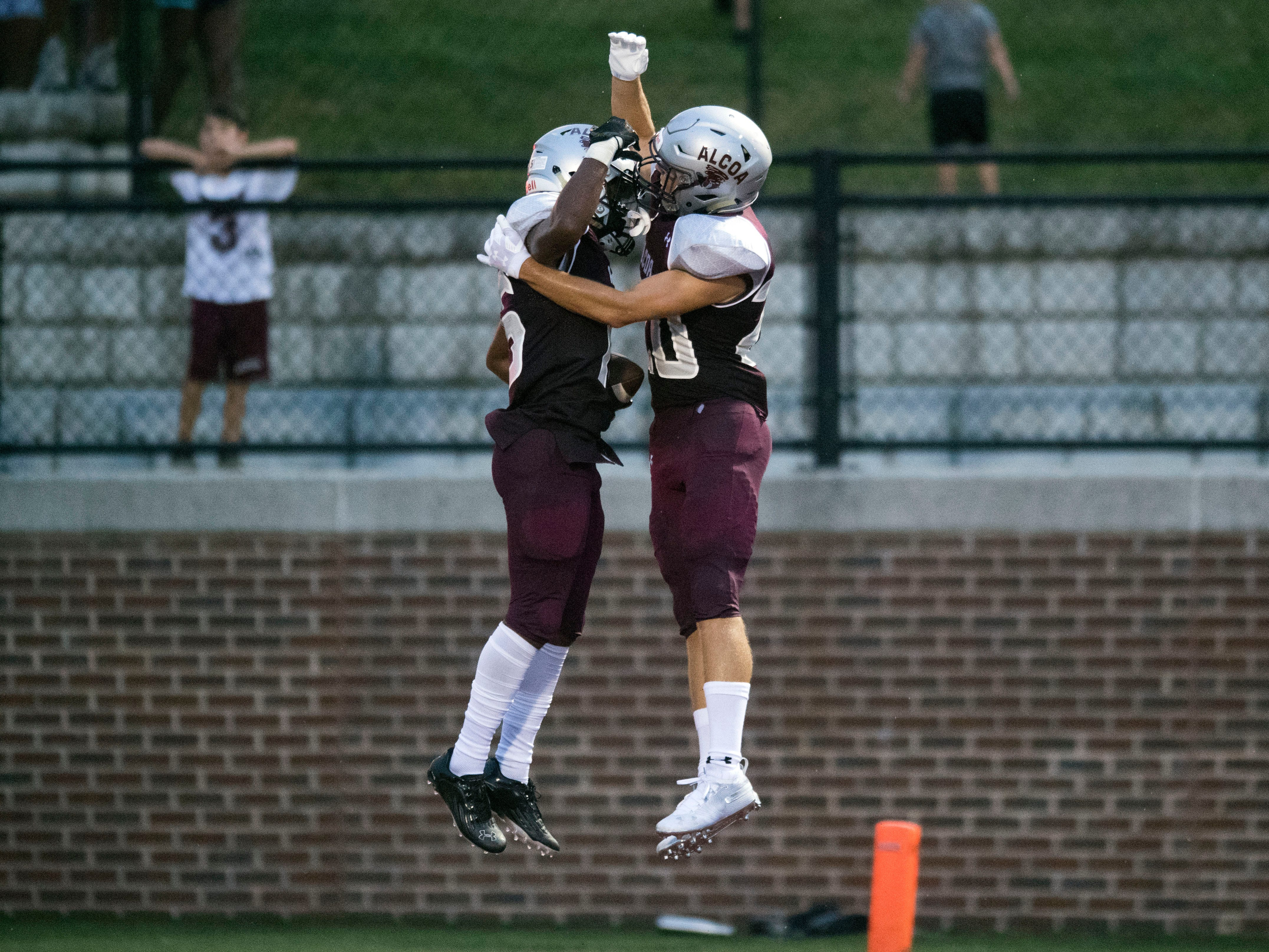 Alcoa's Ahmaudd Sankey (15) and Tyler Boyd (20) celebrate after Sankey ran the ball for a touchdown in the football game against Grace Christian Academy on Thursday, August 16, 2018.