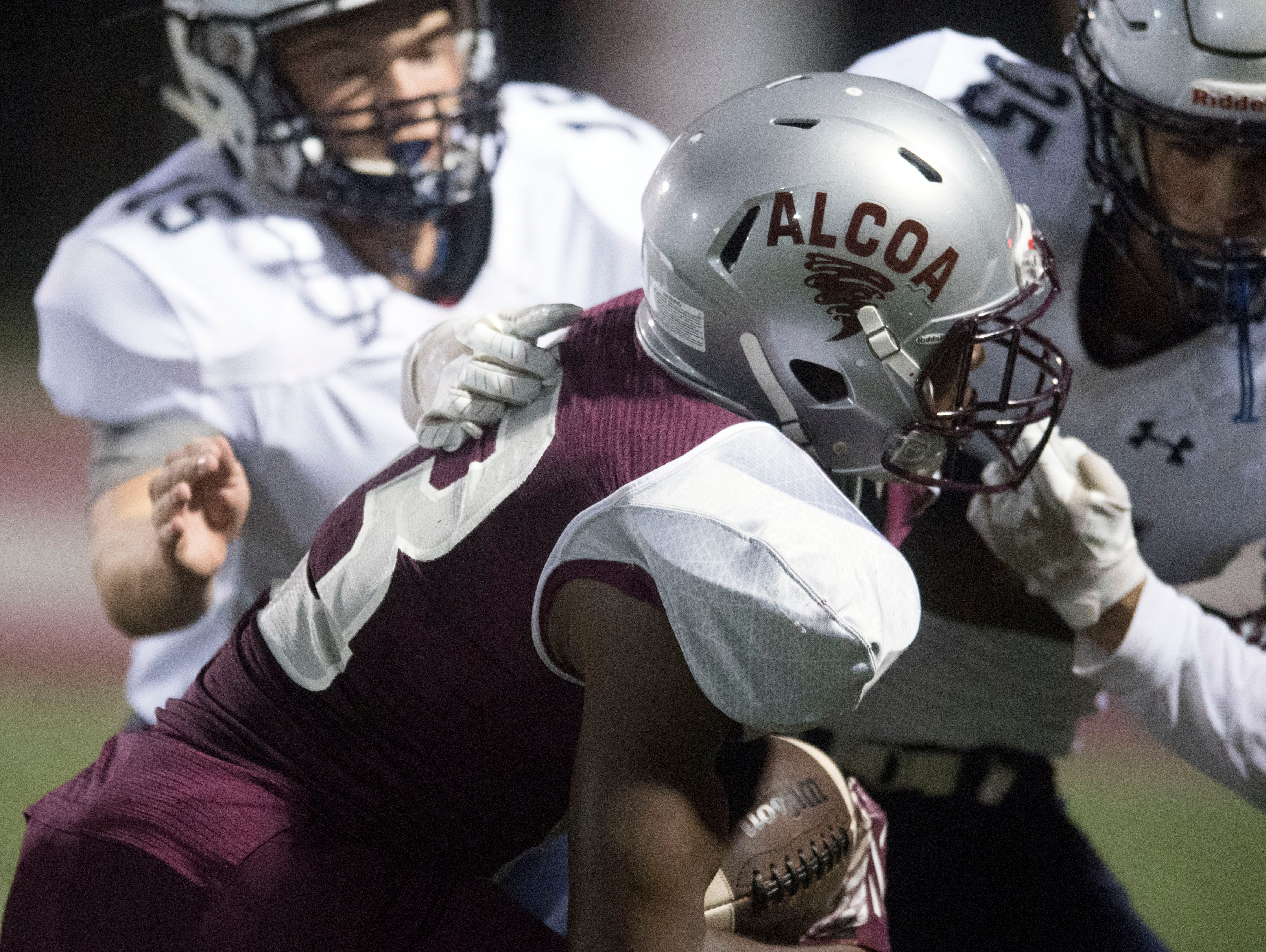 Alcoa's Ronald Jackson (13) is pulled down by Grace Christian Academy's Ty Carter (35) during the football game at Alcoa on Thursday, August 16, 2018.