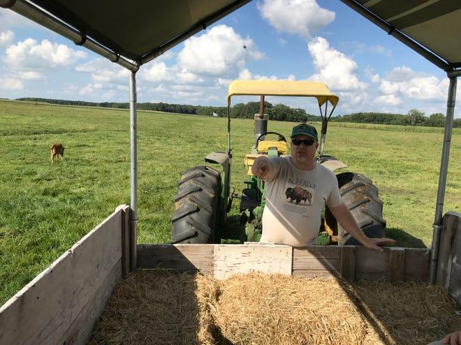 Troy Van Meter drives the tractor at Van Meter Buffalo Ranch in Monticello.