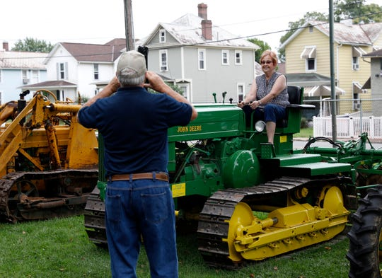Ron Leopold, left, from Glandorf, takes a photograph of his wife Marty Leopold as she sits on a custom made John Deere crawler Friday, Aug. 17, 2018, at the Fairfield County Antique Tractor Club's annual show at the Fairfield County Fairgrounds in Lancaster.