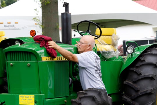 Mike Smith, from Marion, wipes water drops off his 1969 John Deere 3020 tractor Friday morning, Aug. 17, 2018, at the Fairfield County Fairgrounds in Lancaster. Smith was showing four of his 40 tractors at the Fairfield County Antique Tractor Club's annual show. The weekend show ends Sunday.