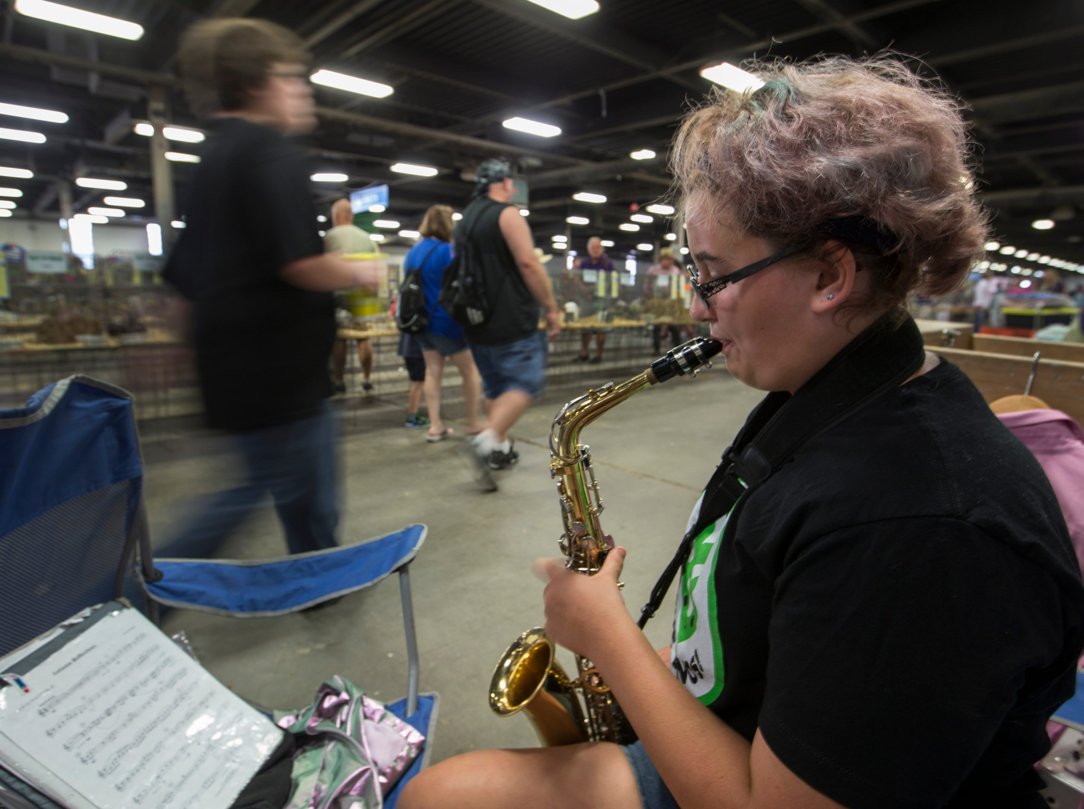 Taylor Fryman, 13, practiced playing the saxophone while keeping a eye on the rabbits she is showing at the Kentucky State Fair. Aug. 17, 2018.