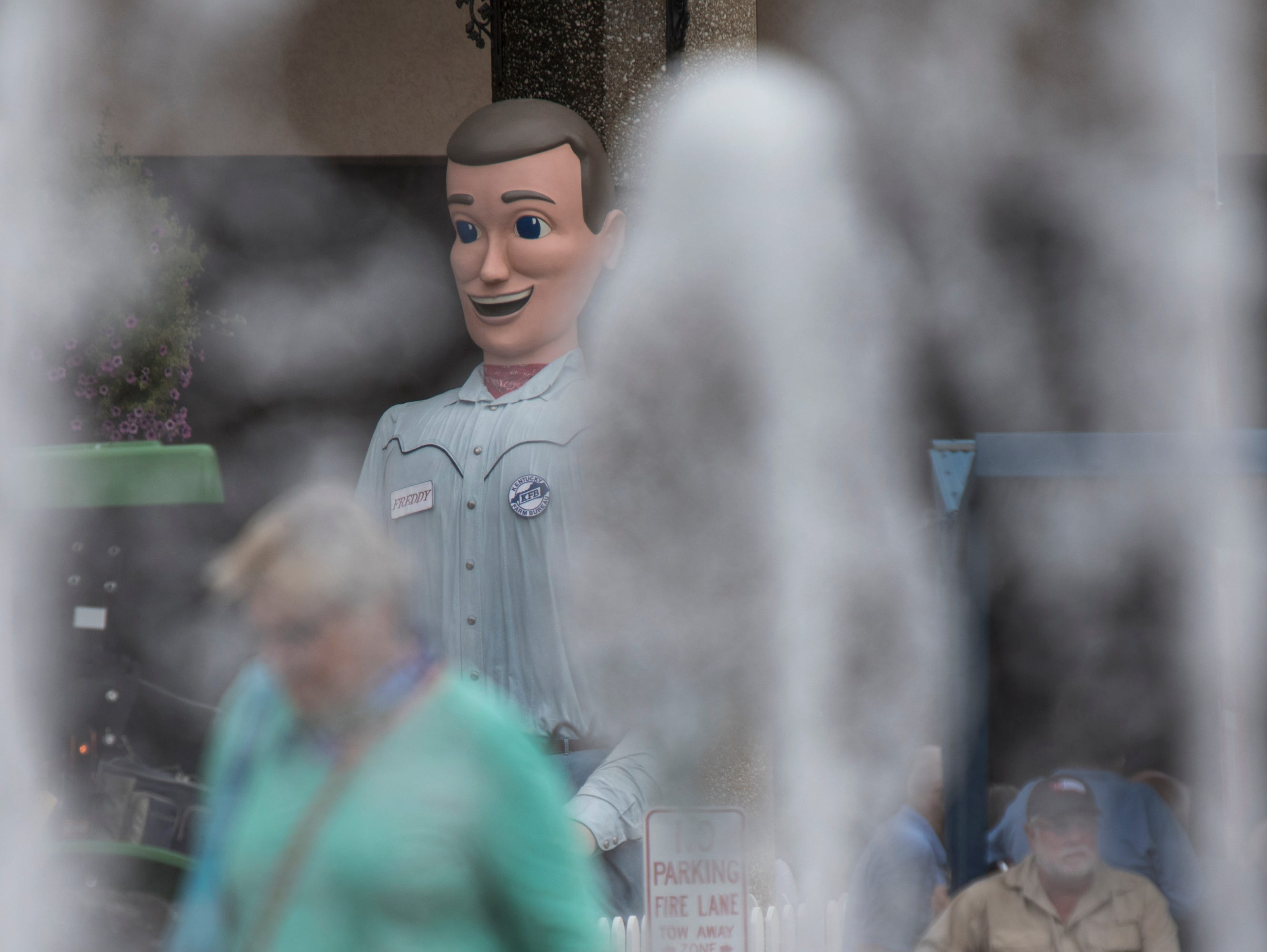 Talking mannequin Freddie Farm Bureau is seen through the mist of the fountain in front of Freedom Hall, at the Kentucky State Fair. Aug. 17, 2018.