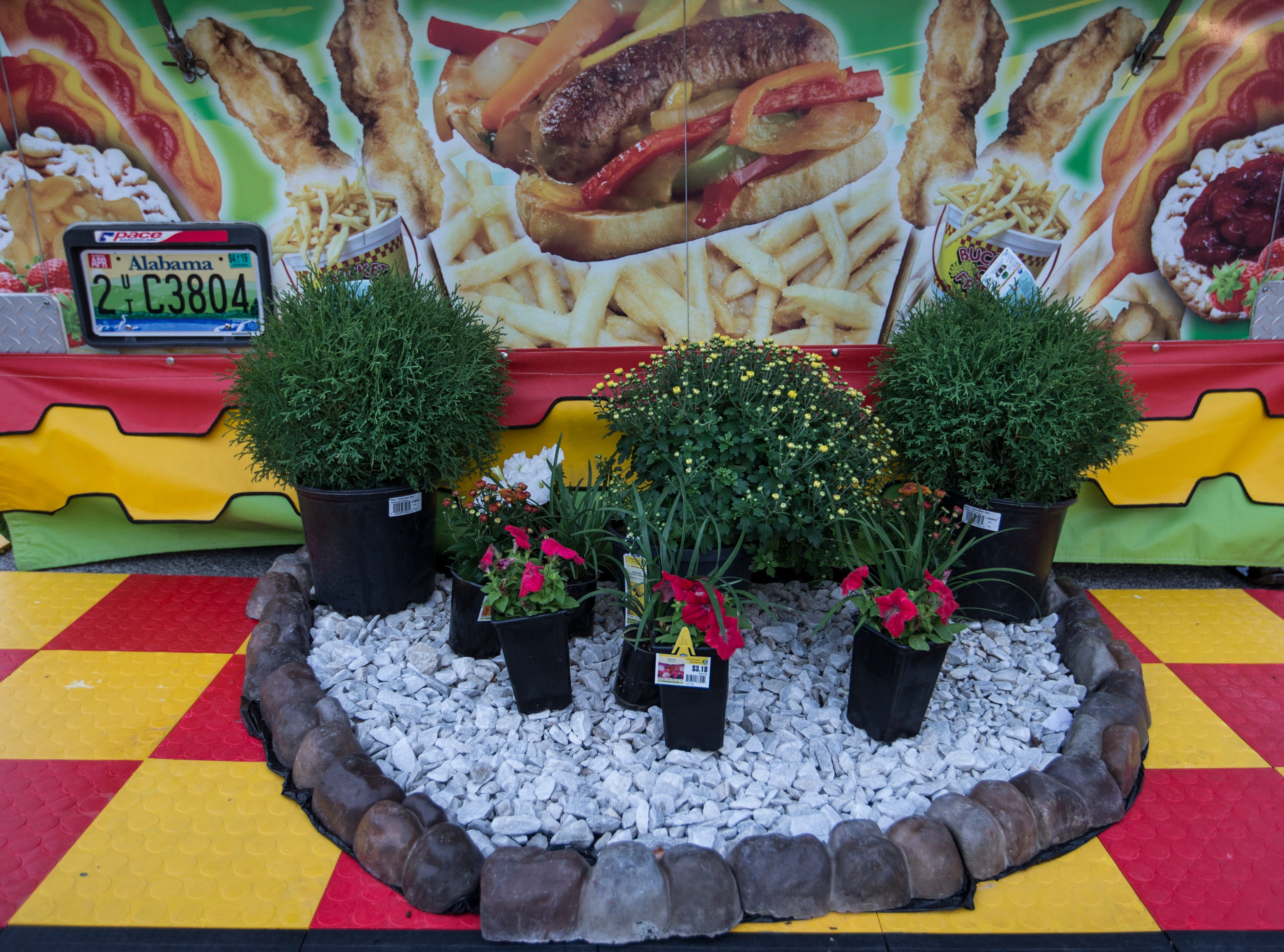 Potted plants decorate a food booth on the midway of the Kentucky State Fair. Aug. 17, 2018.