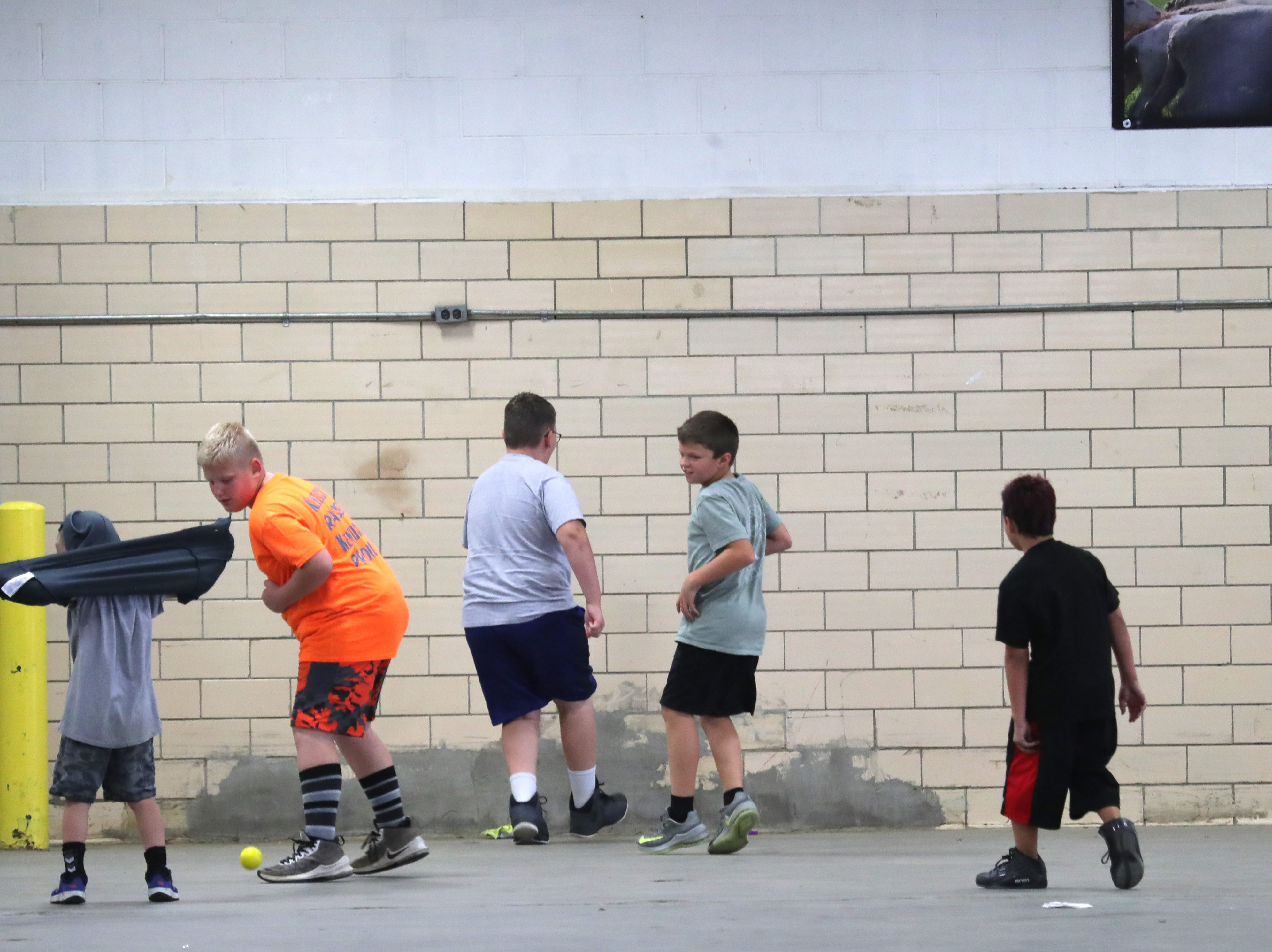 Kids find a ball and a wall to entertain themselves in the livestock area of the Kentucky State Fair.