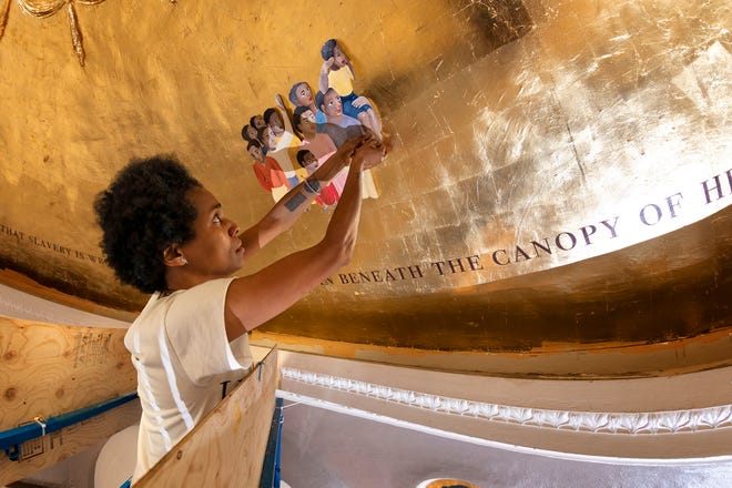"""Artist Karyn Olivier, of Philadelphia, worked placing part  of her piece entitled """"Witness"""" on the domed ceiling in the atrium at Memorial Hall  on August 15, 2018."""