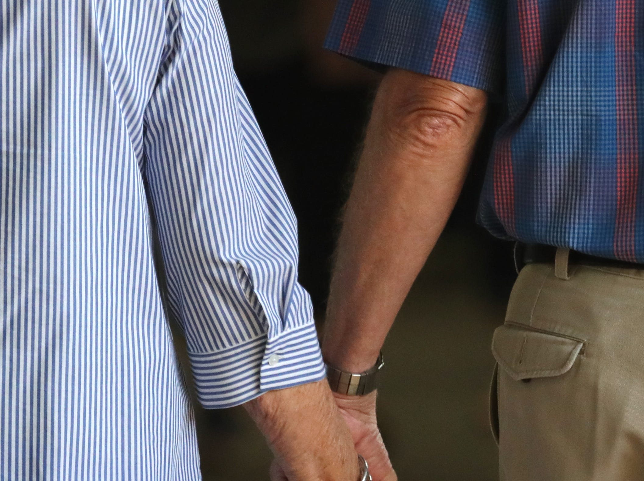 A couple hold hands as the walk through the livestock area of the Kentucky State Fair.