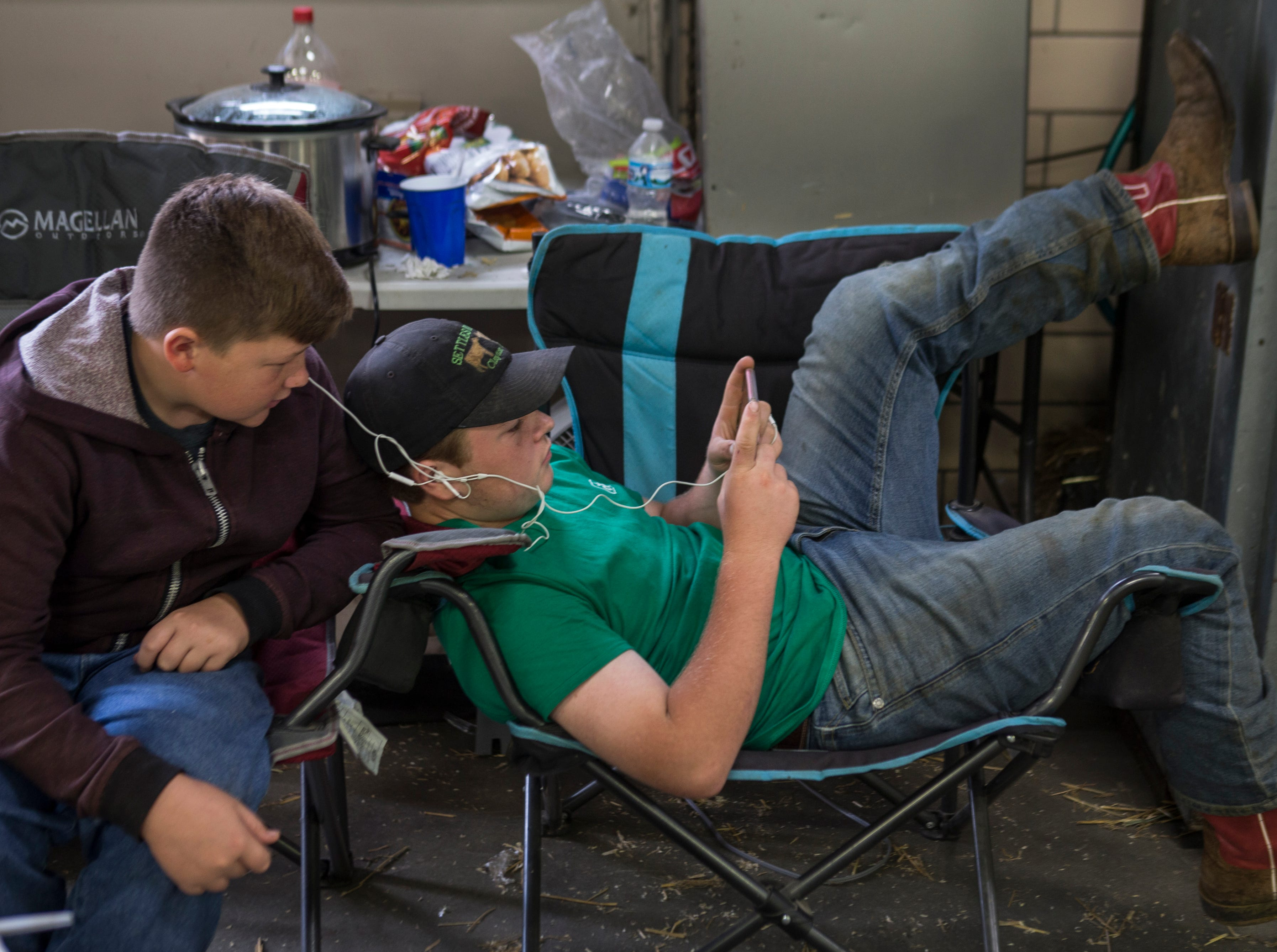 Carter Settles, 13, right, played a video game on his phone while Dillon Freeman, 14, looked on. The boys were showing their dairy cattle at the Kentucky State Fair. Aug. 17, 2018.