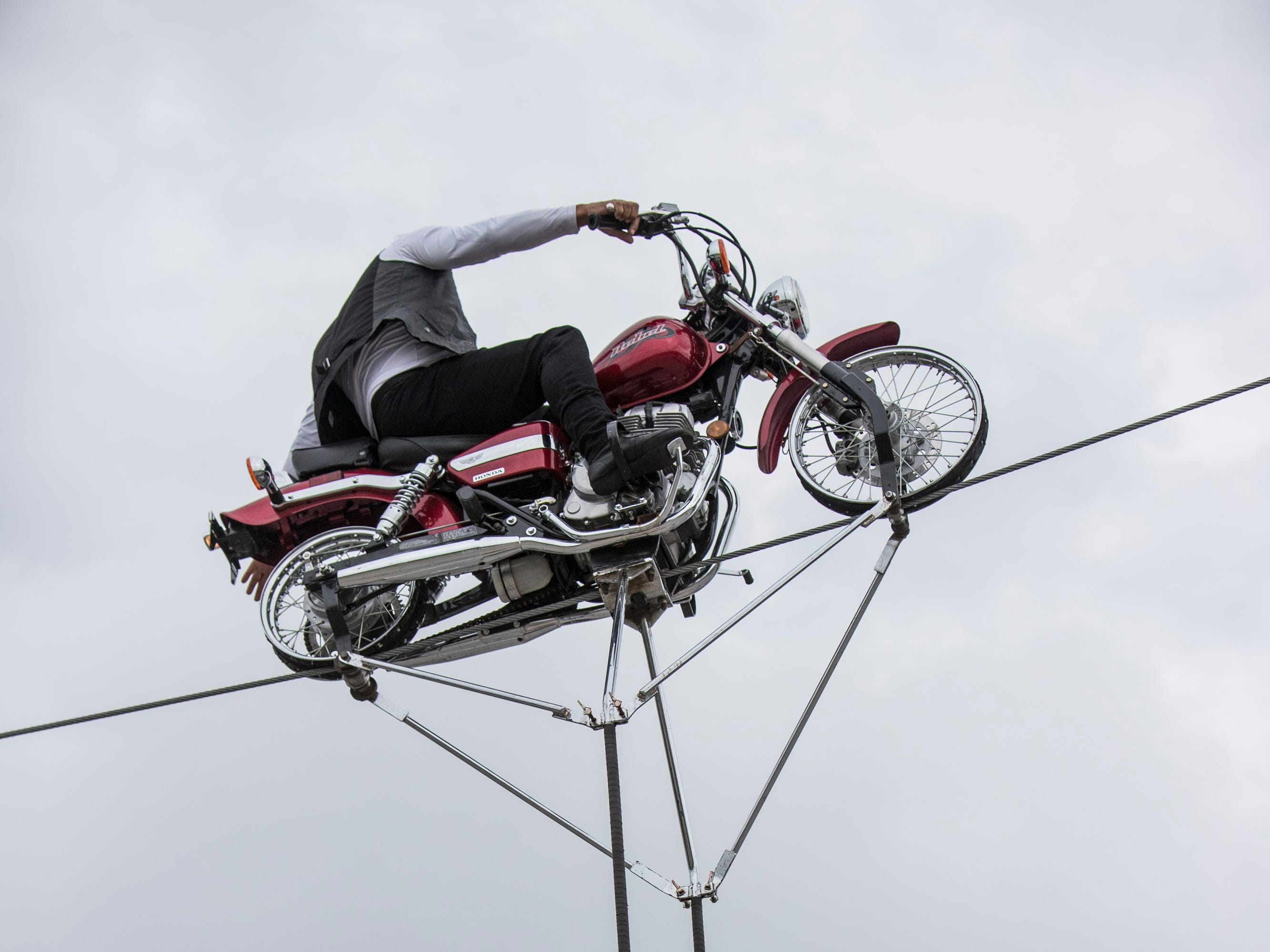 Noe Espana balanced a motorcycle on a high wire while Vivien Espana dangled from a hanging trapeze during a performance by the Motor Maniacs, at the Kentucky State Fair. Aug. 17, 2018.
