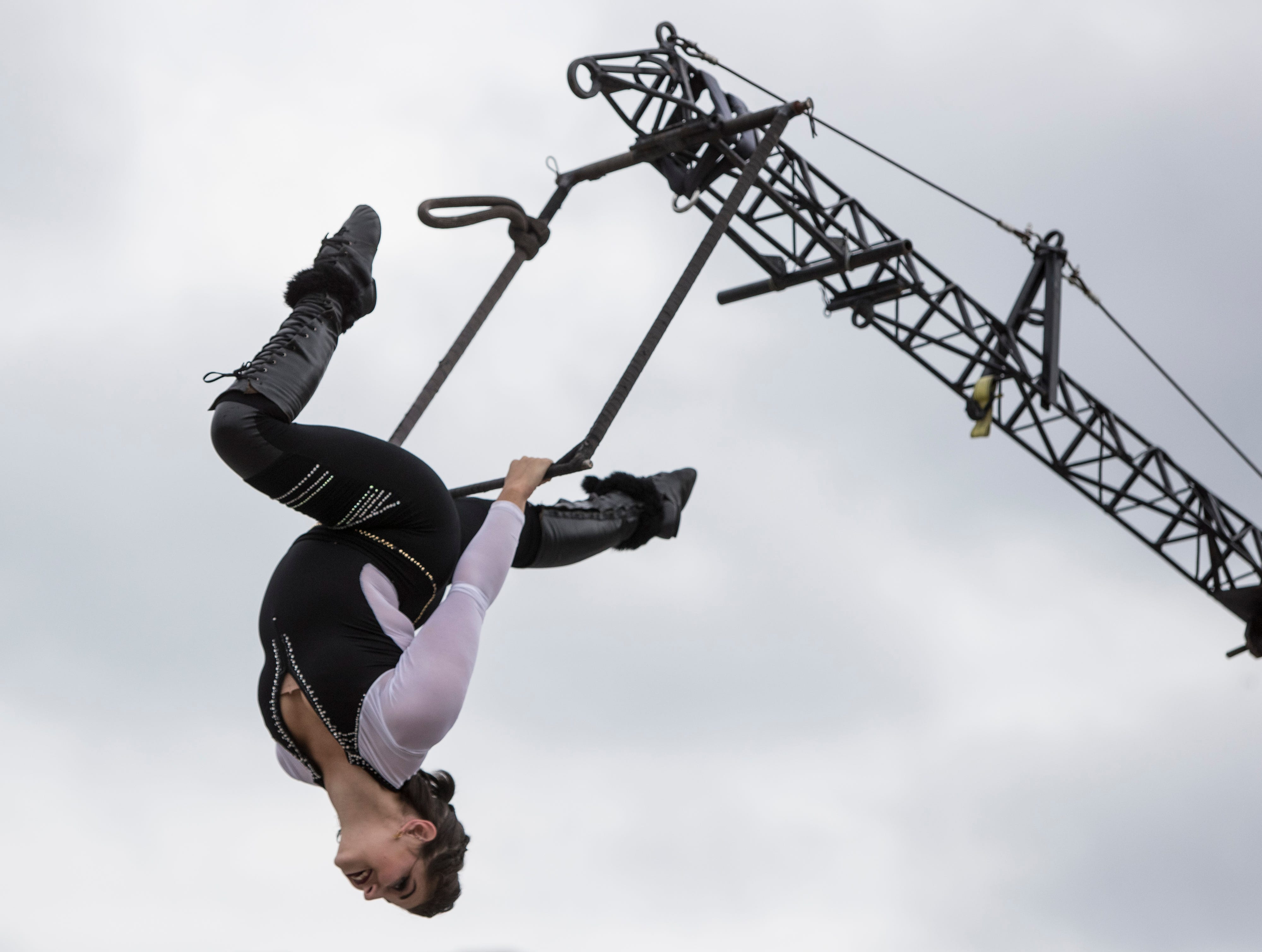 Ivory Young of the Motor Maniacs show performed a moving trapeze act while being spun from a motorbike at the Kentucky State Fair. Aug. 17, 2018.