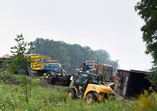 Workers clean up the scene of an accident Friday, Aug. 17, 2018, on westbound I-96 near exit 122 in Leroy Township.  Around 4:50 AM, a semi carrying watermelons sideswiped a disabled semi stopped along the shoulder according to Ingham County Sheriff Department officials.  The driver of the parked semi was taken to Sparrow with serious but non life-threatening injuries.