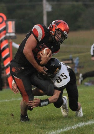 Lucas quarterback Jeb Grover is tackled by Northmor's Noah Trainer last season. Trainer is part of a super senior class at Northmor that graduated in 2017.