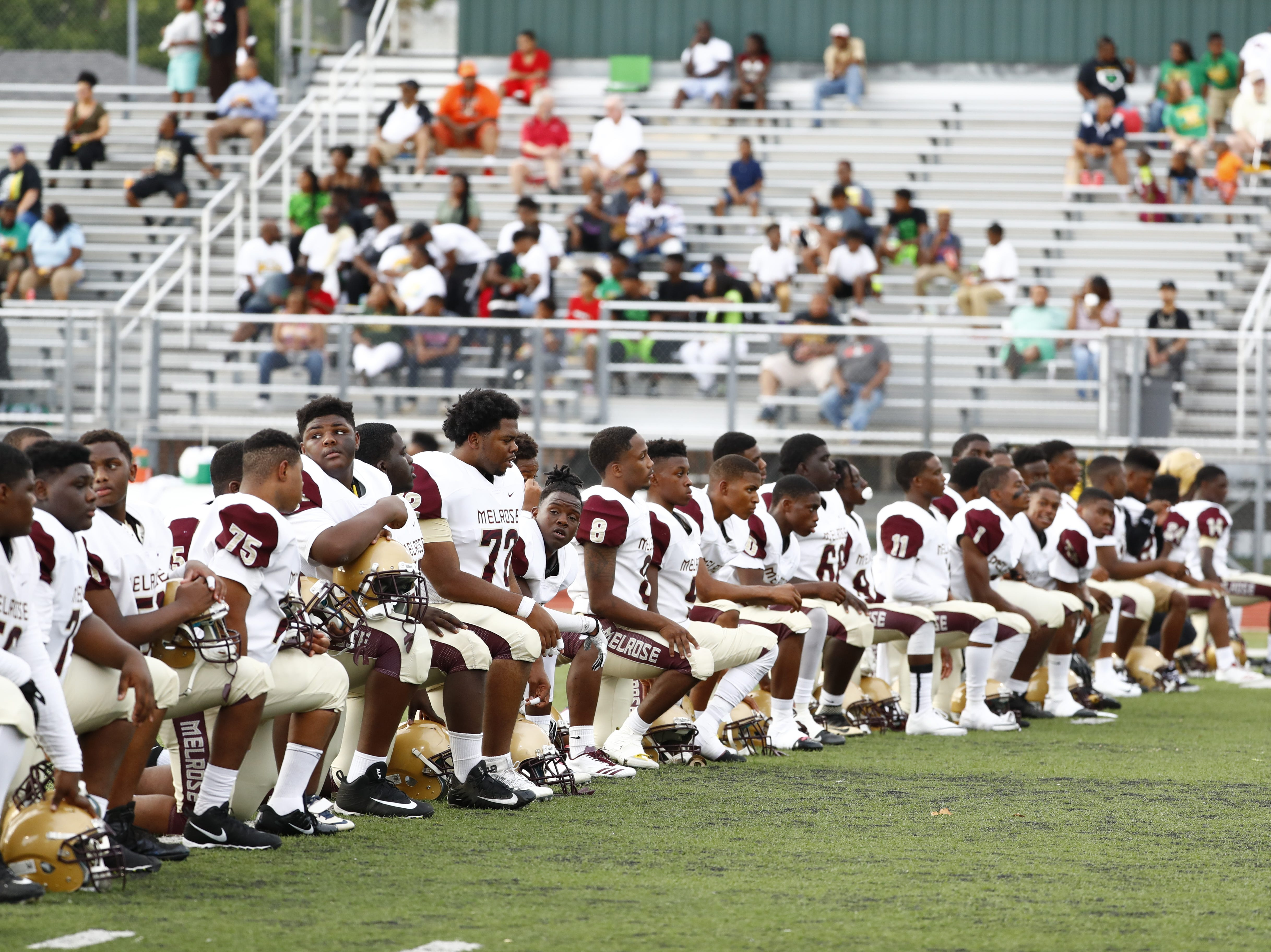 Melrose football players kneel during warm-ups prior to Friday's season-opening game at Central on Aug. 17, 2018.