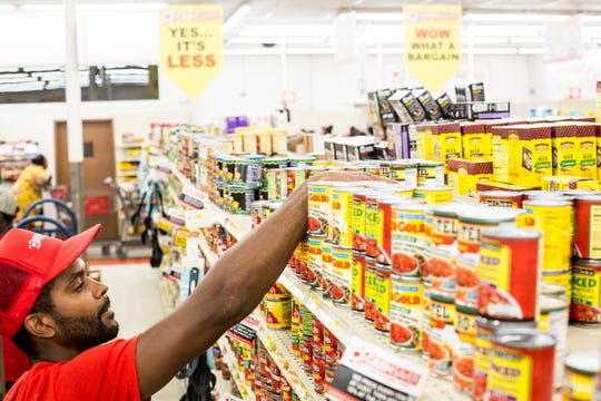 """Cash Saver employee Josh Bowe restocks shelves on Aug. 14. """"It's so hard to keep things on the shelves,"""" Bowe said about how busy the store has been since it opened."""