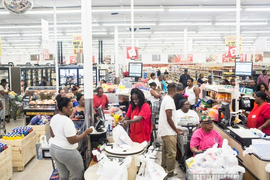 Cashiers attempt to keep up with the large crowd at the new Cash Saver supermarket.