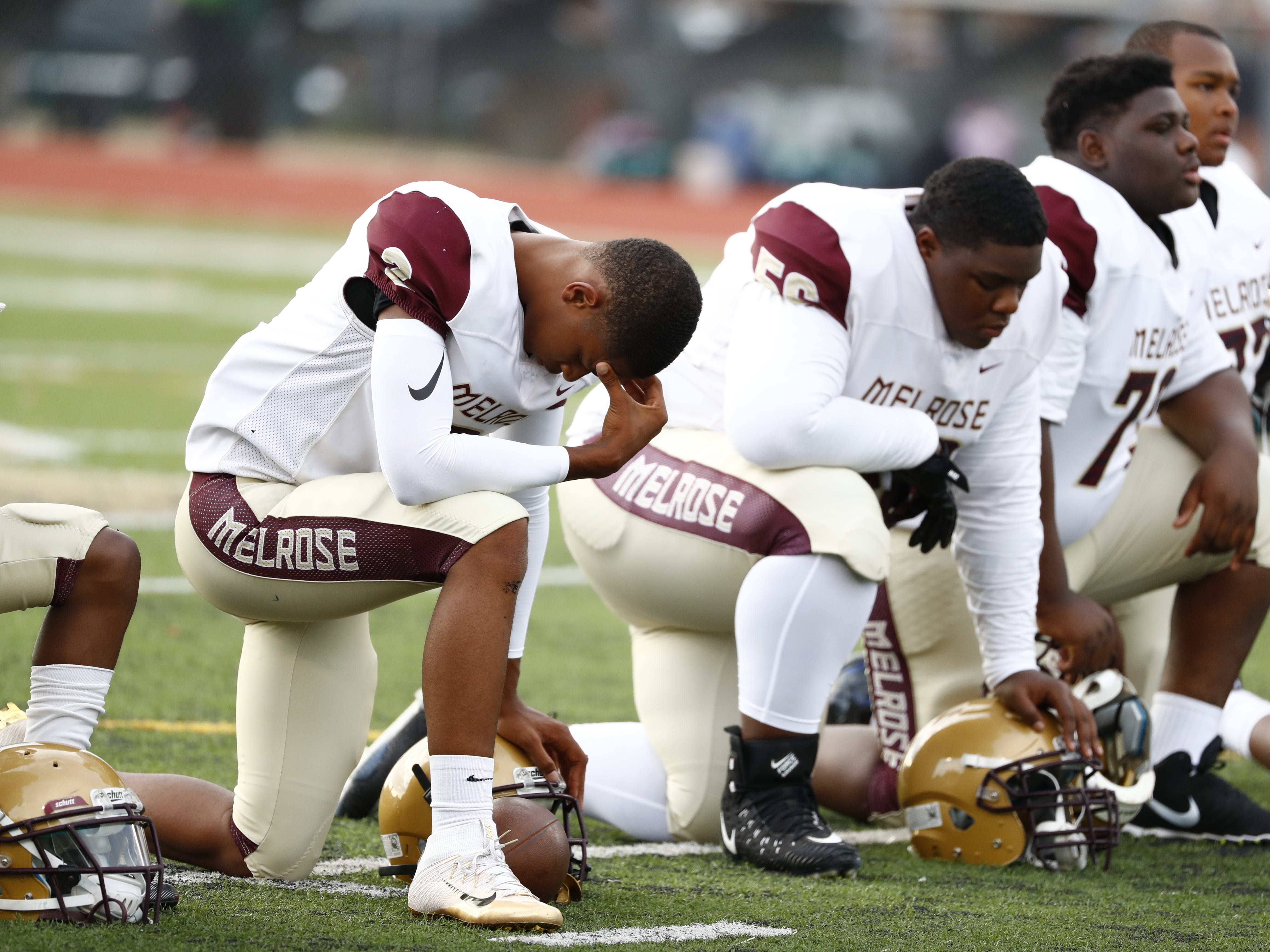 Melrose's William Mason, left, prays prior to Friday's season-opening football game at Central on Aug. 17, 2018.