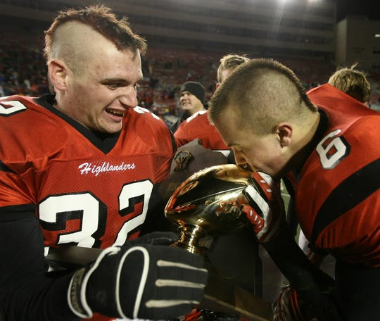 Homestead's Mike Pelisek hold the trophy for #6 Andy Boll as he gives it kiss after their win over 13-11 Arrowhead in their Division 1 Championship game Friday, November 21,2008, at Camp Randall Stadium in Madison WI.