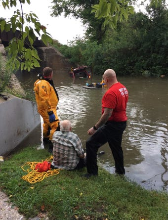 A  man is rescued by the Watertown Fire Department after he drove his car around a barricade and float into a flooded street in Watertown.