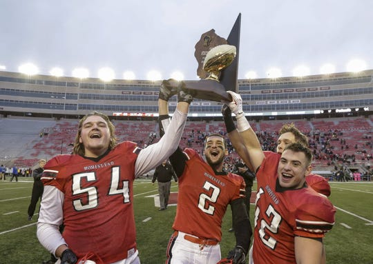 Homestead's Josh Mueller (54), Jack Popp (2), Jack Bruner and Matt Winters (42) celebrate with the WIAA Division 2 championship trophy after Homestead beat Waukesha West 28-12.