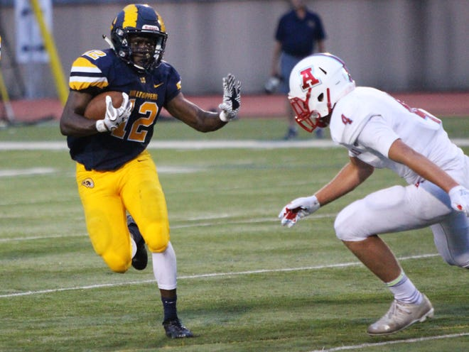 Marquette senior running Daeleon Brown-Williams stiff arms an Arrowhead defender during a game on August 16 at Hart Park.