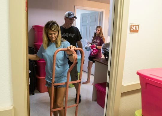 LaDonna, left, and Stacy Atkins, help their daughter Taitum, of Harleton, Texas, help bring belongings into her dorm during returning student move-in at University of Louisiana at Monroe on August 17 in Monroe, La.