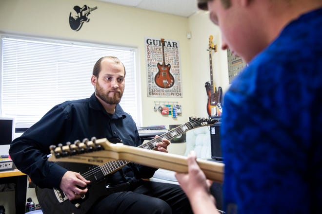 Nick Rogers, the lead guitar, bass and ukulele instructor, works with Devin Manley, 17, during his bass guitar lesson at Connor School of Music in Naples on Tuesday, August 14, 2018.