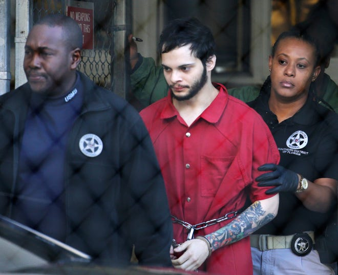 In this Jan. 30, 2017, file photo, Esteban Santiago, center, is led from the Broward County jail for an arraignment in federal court in Fort Lauderdale.