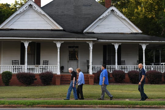 Jimmy and Rosalynn Carter walk home with Secret Service agents along West Church Street after having dinner at a friend's house in Plains, Ga., their hometown.
