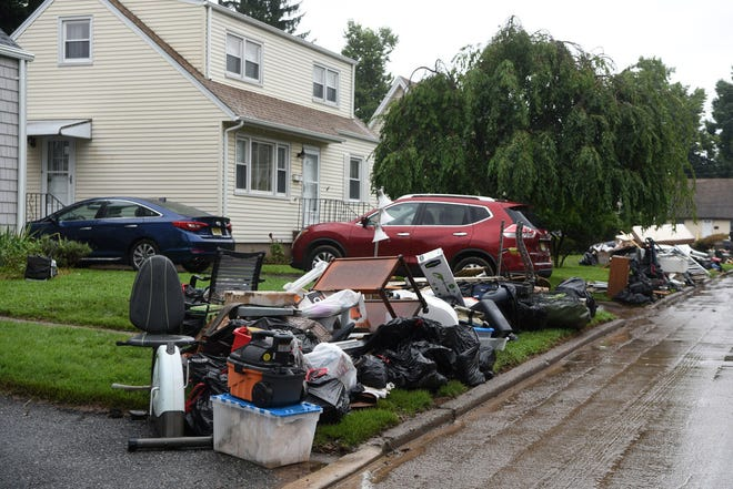 Items ruined in the flood removed from homes on Ryle Avenue in Little Falls sit on the street on Aug. 13.