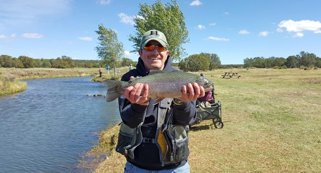 """Disabled veteran Ray Kirby, of Las Cruces, shows off a rainbow trout he caught during a fishing trip to Show Lo, Arizona, sponsored by Project Healing Waters, a group that helps disabled vets recover through the """"therapeutic benefits of fly fishing."""""""